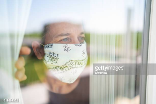 mature adult woman with mouse nose mask looking out through the window - avoidance stock pictures, royalty-free photos & images