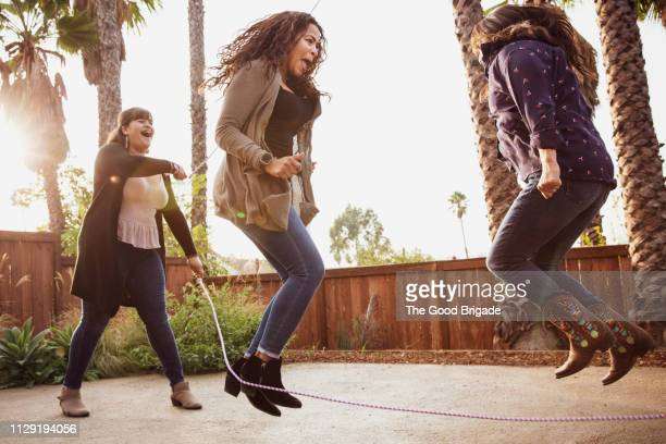 mature adult women jumping rope in backyard - skipping rope stock pictures, royalty-free photos & images
