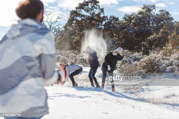 mature adults mixed ethnic friends on an outdoor colorado adventure snowball fight - ducking stock pictures, royalty-free photos & images