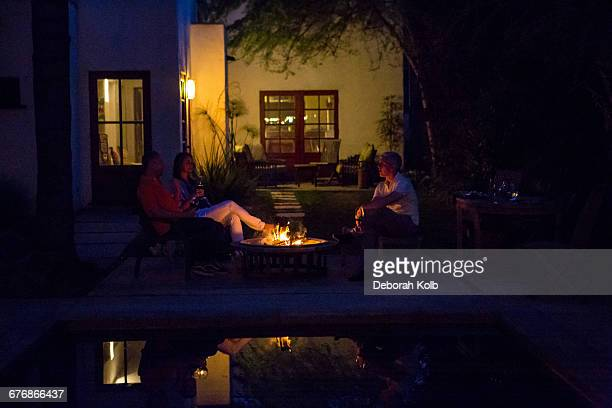 Mature adults relaxing by patio fire at dusk