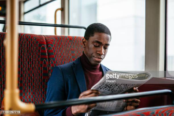 Mature African American businessman commuting and reading newspaper