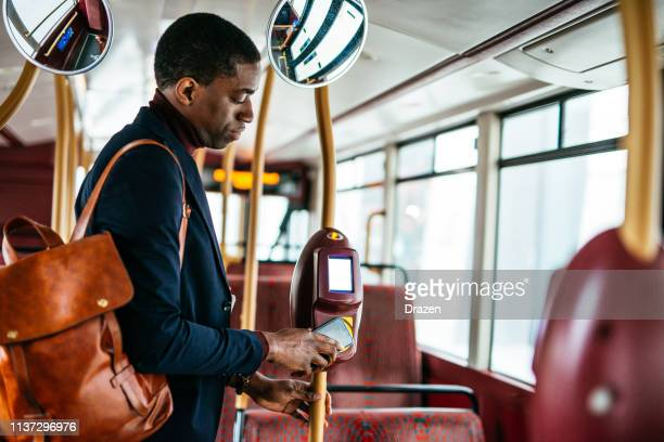 Mature African American businessman using phone for contactless payment.