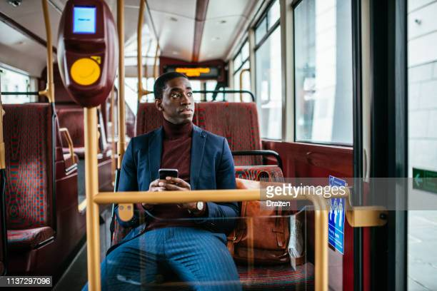 Mature African American businessman using phone while going to work by bus
