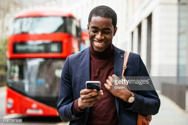 Mature African American businessman using phone while going to work.
