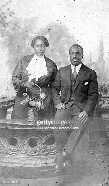 Mature African American couple man and woman the man seated on a countertop wearing a suit the woman standing behind the counter top and holding a...