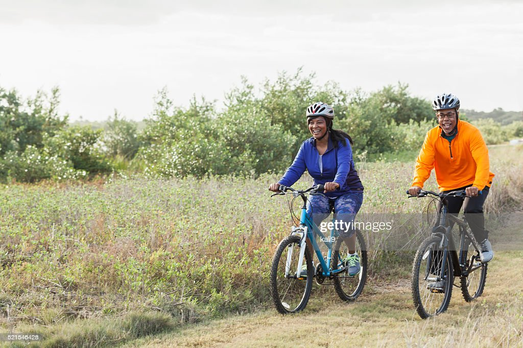 Mature African American couple riding bikes in park : Stock Photo