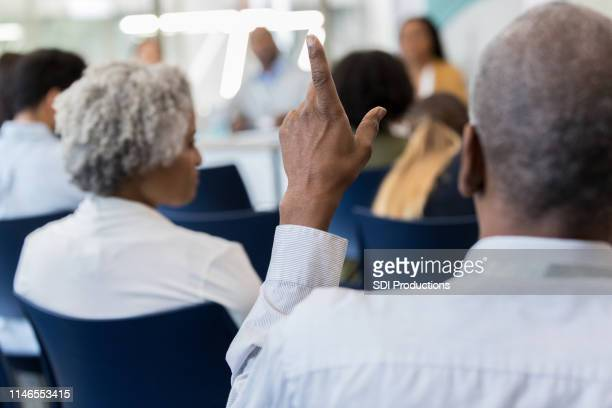 mature african american man questions speaker - town hall stock pictures, royalty-free photos & images