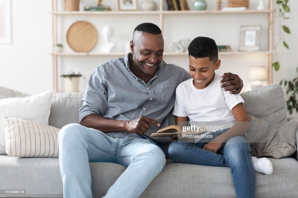 Mature african american man reading book with his grandson at home : Stock Photo