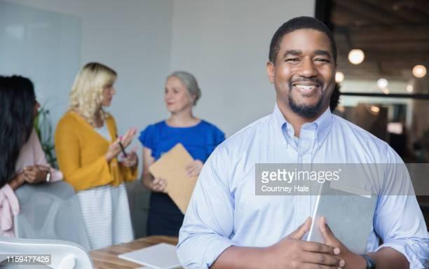 o homem maduro do americano africano sorri ao estar no quarto de placa com colegas - afro americano - fotografias e filmes do acervo