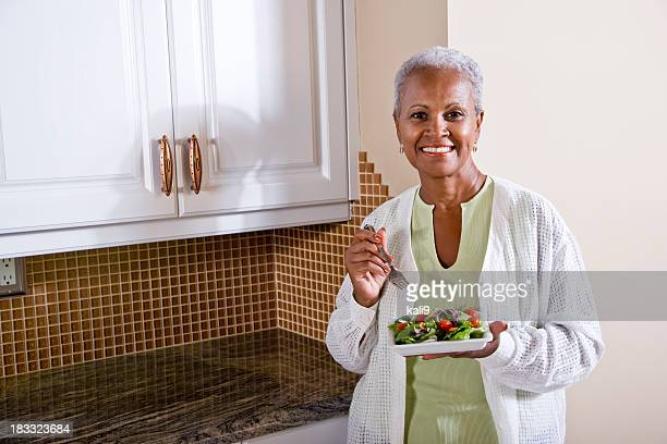 Mature African American woman eating salad in kitchen