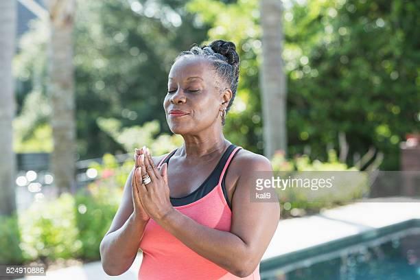Mature African American woman meditating outdoors