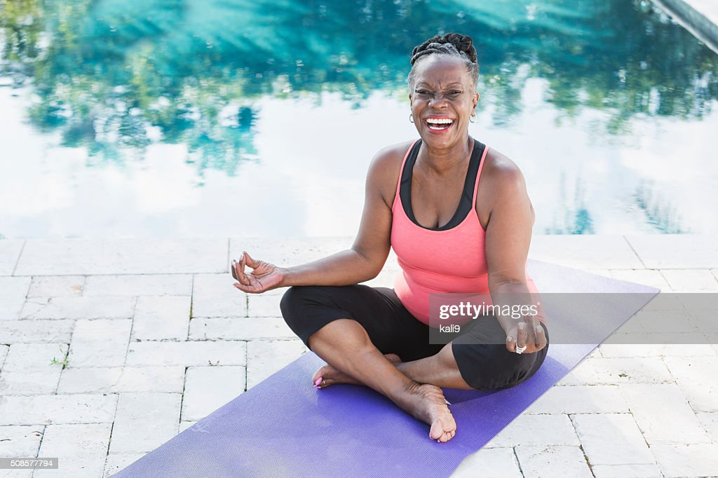 Mature African American woman on yoga mat by pool : Stock Photo