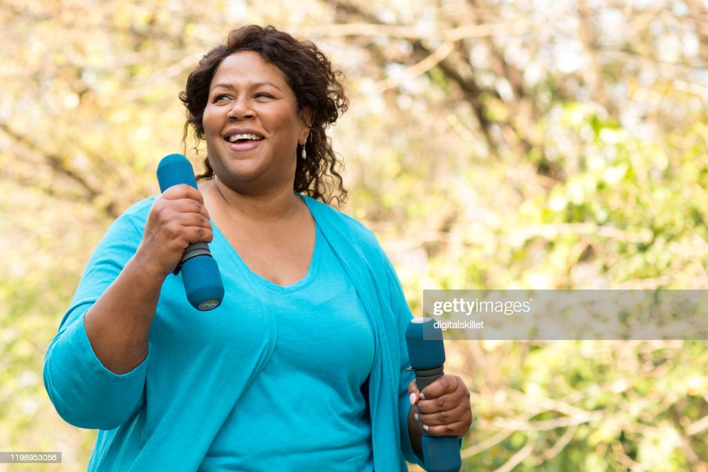 Mature African American woman smiling and exercising. : Stock Photo