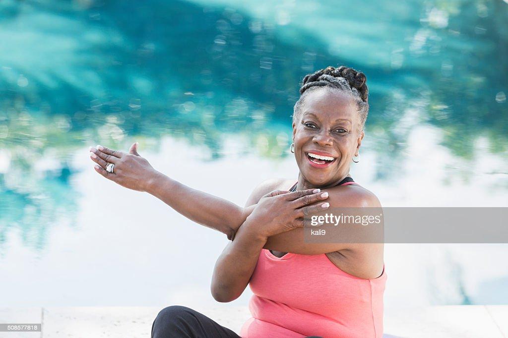 Mature femme afro-américaine s'étendant au bord de la piscine : Photo
