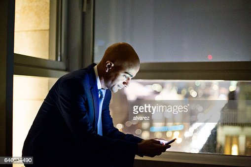 Mature african businessman in office lobby using cell phone