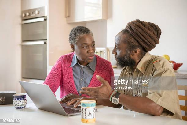 Mature African couple using laptop and discussing