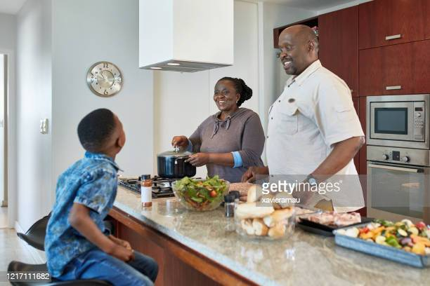 mature african grandparents smiling at grandson in kitchen - chubby granny stock pictures, royalty-free photos & images