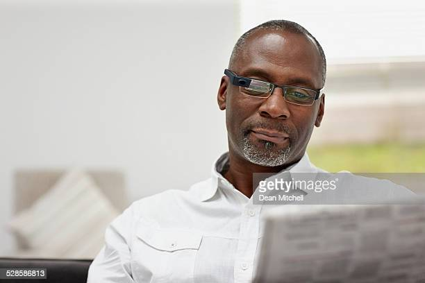 mature african man wearing smart glasses reading newspaper - handsome 50 year old men stock photos and pictures