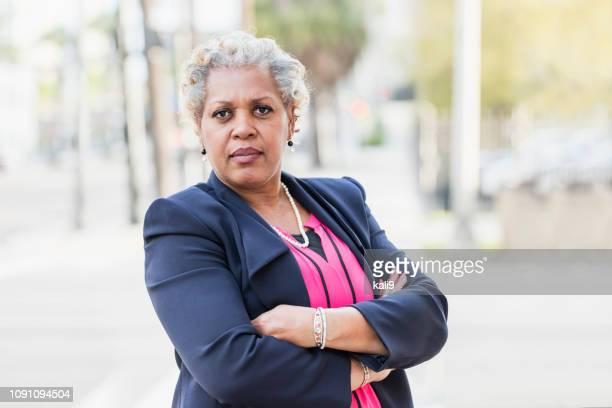 reife afroamerikanischen geschäftsfrau, arme verschränkt - heck stock-fotos und bilder