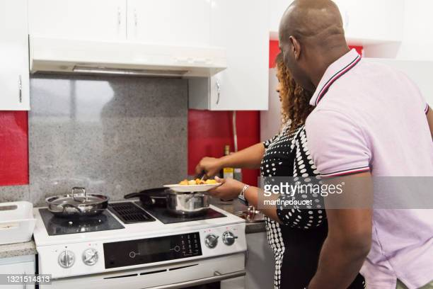"""mature african-american couple cooking meal in kitchen. - """"martine doucet"""" or martinedoucet stock pictures, royalty-free photos & images"""