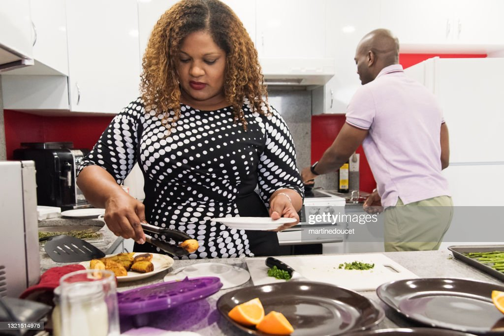 Mature African-American couple cooking meal in kitchen. : Stock Photo