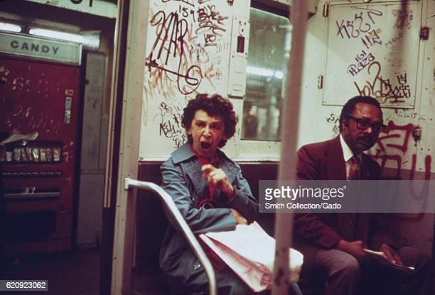 A mature AfricanAmerican man and a mature Caucasian woman sit inside a subway car which has been extensively marked with graffiti New York City New...
