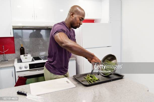 """mature african-american man cooking meal in his kitchen. - """"martine doucet"""" or martinedoucet stock pictures, royalty-free photos & images"""