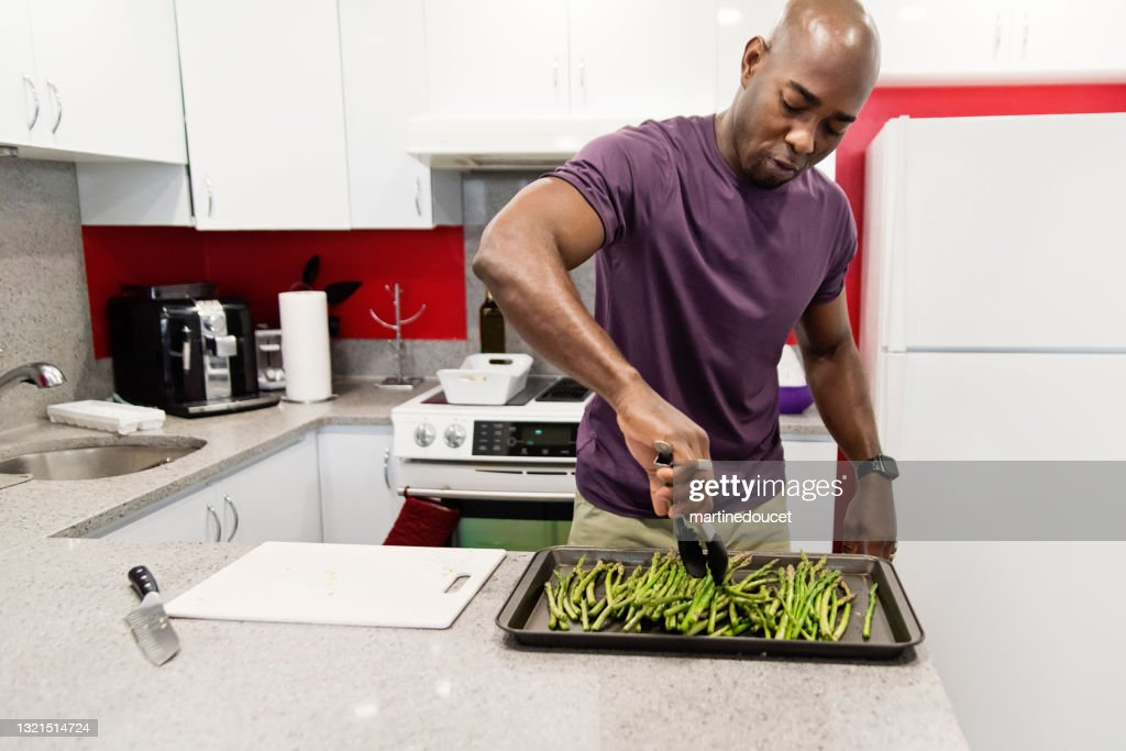 Mature African-American man cooking meal in his kitchen. : Stock Photo