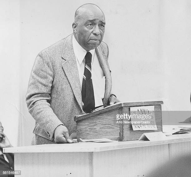 A mature AfricanAmerican man in a suit speaking from a lectern on a stage 1953