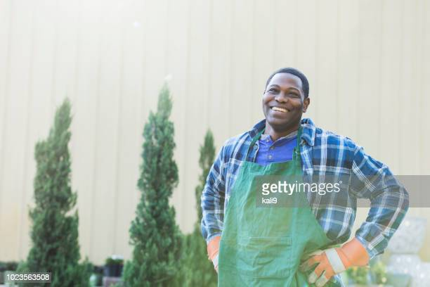 mature african-american man working in plant nursery - grounds stock pictures, royalty-free photos & images