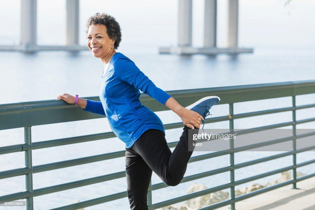 Volwassen Afro-Amerikaanse vrouw uit te oefenen op de waterkant : Stockfoto