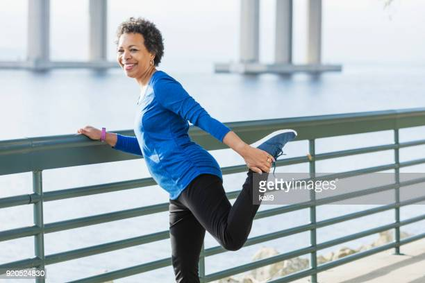 mature african-american woman exercising on waterfront - stretching stock pictures, royalty-free photos & images