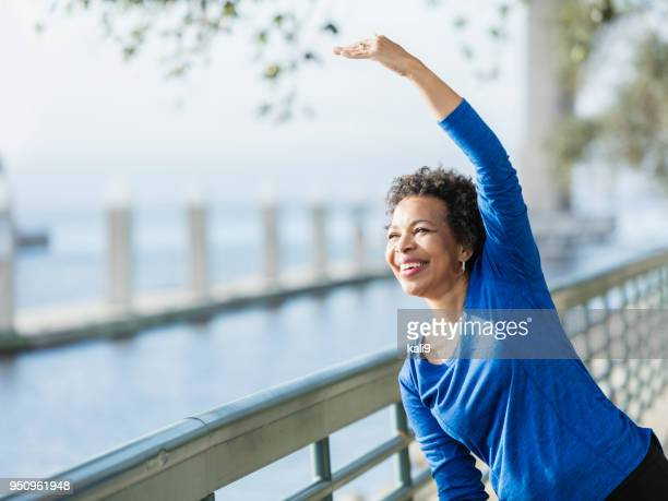 mature african-american woman exercising on waterfront - african american ethnicity imagens e fotografias de stock