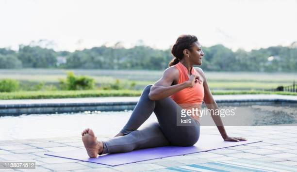 mature african-american woman exercising, stretching - black pants stock pictures, royalty-free photos & images