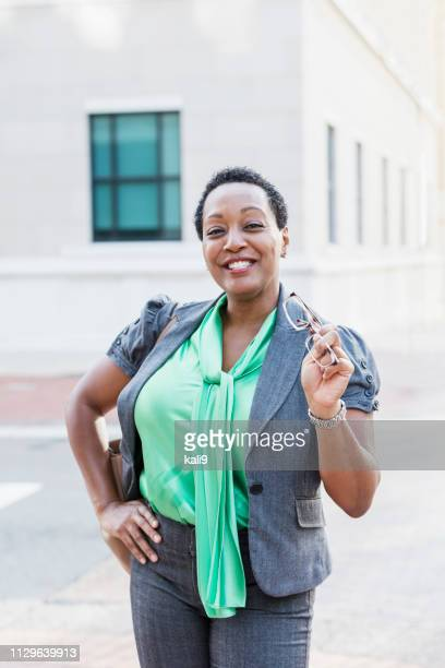 mature african-american woman in city, hand on hip - short hair for fat women stock pictures, royalty-free photos & images