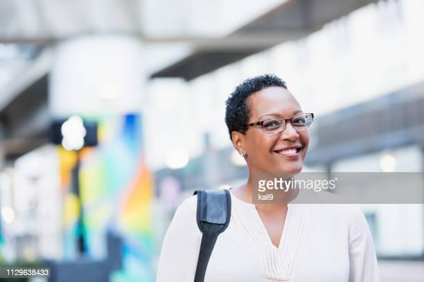 mature femme afro-américaine, marchant sur la rue de la ville - 45 49 ans photos et images de collection