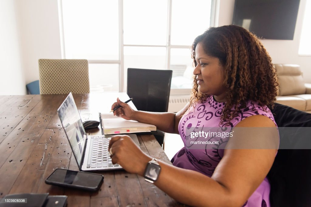 Mature African-American woman working from home in teleconference. : Stock Photo