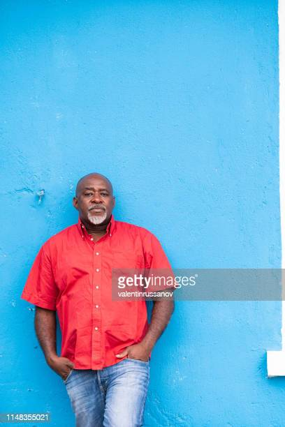 mature afro man portrait on blue background - man blue background stock pictures, royalty-free photos & images