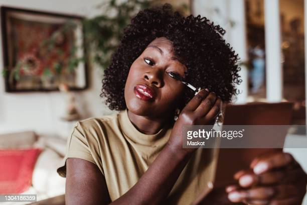 mature afro woman applying mascara at home - mascara stock pictures, royalty-free photos & images