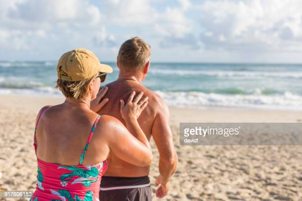 Mature aged couple putting on sunscreen at the beach
