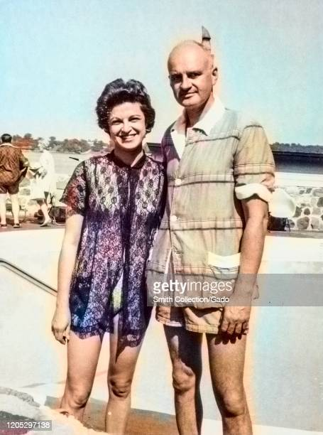 Mature American tourist couple posing in front of a swimming pool with woman wearing a bathing suit and coverup and man wearing shorts and a shirt...