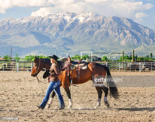 mature american woman walks horse on ranch in spanish fork utah - spanish fork utah stock pictures, royalty-free photos & images