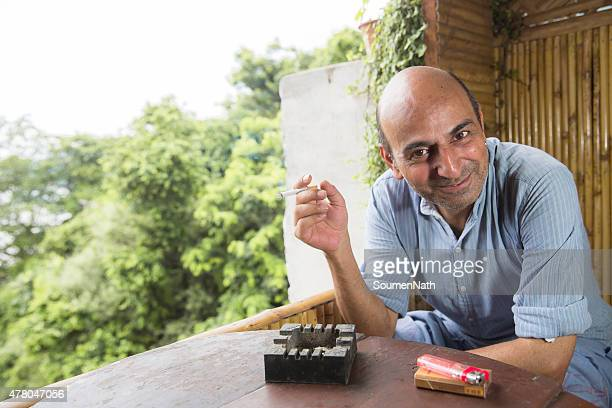 Mature and bald man smoking a cigarette