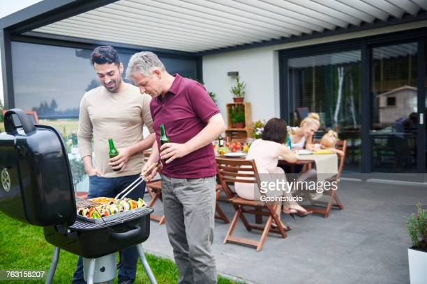 mature and mid adult man barbecuing at family lunch on patio - mid volwassen mannen stockfoto's en -beelden