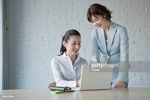 Mature and mid adult women using laptop at table