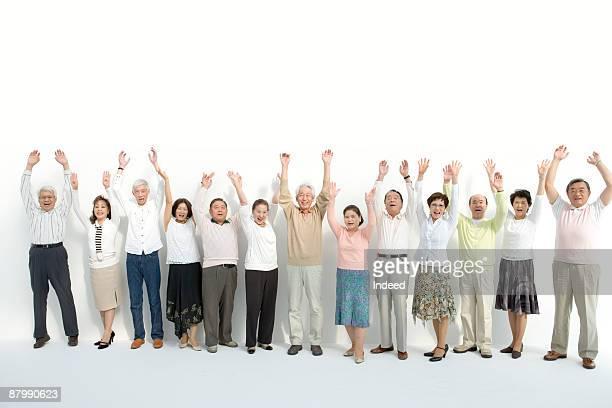 Mature and senior people raising arms, portrait