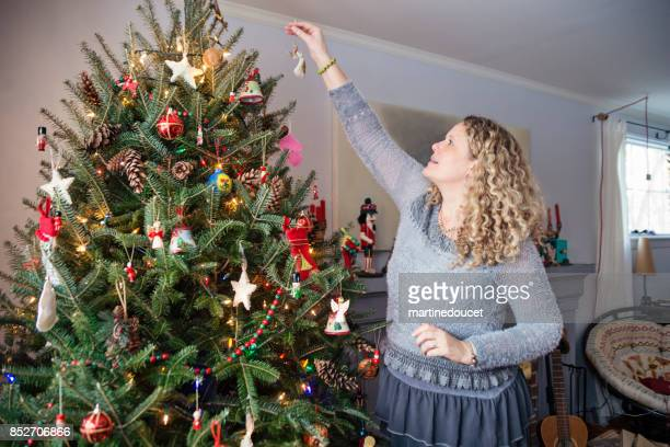 Mature and tall woman decorating Christmas tree at home.