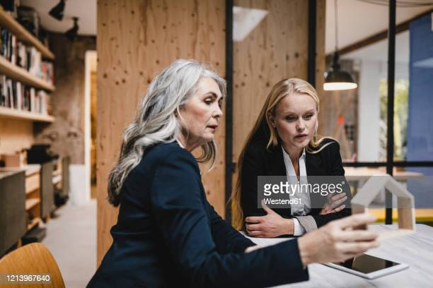 mature and young businesswoman examining architectural model in loft office - 後任 ストックフォトと画像