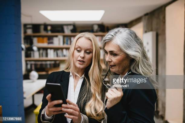 mature and young businesswoman using smartphone in loft office - 後任 ストックフォトと画像