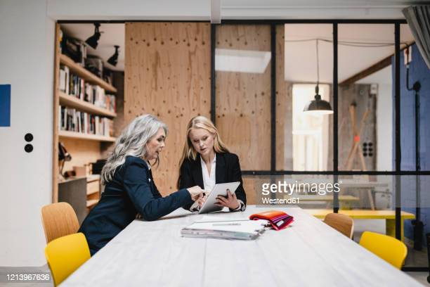 mature and young businesswoman using tablet in loft office - 後任 ストックフォトと画像